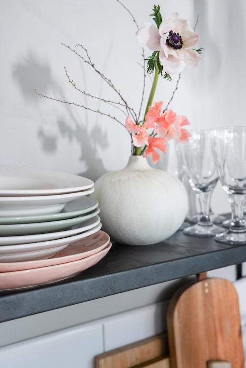 Pastellfärgade tallrikar, Rusta och Åhléns. Vinglas, Ikea. Skärbräda, Rusta.  Vas och blommor, Pom Pom.
