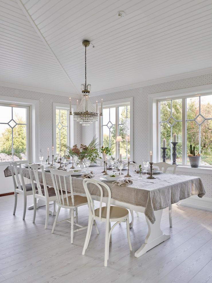 """""""Vi är så glada för vårt stora bord, här får vi plats många och det gillar vi"""", säger Elin. Paret har fått hjälp av en god vän att bygga det stora matsalsbordet. Utgångspunkten till bordet var ett gammalt bordsunderrede. Duken är sydd av metervara från Tygskroten i Skene."""