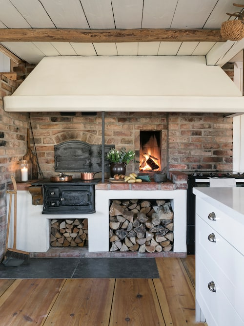 Huset har fem eldstäder. I köket finns en vedspis, en öppen eldstad och även en ugn där familjen gärna bakar pizza.