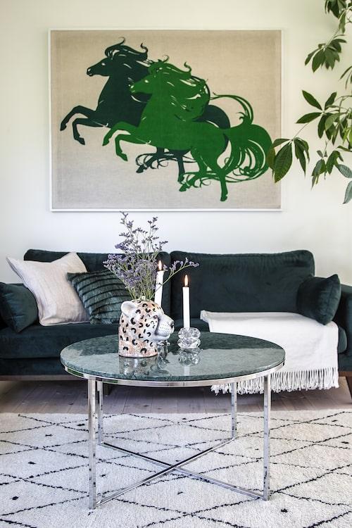 Cornelia erkänner att valet av en 3-sitssoffa till ett hushåll på fyra personer var ett val av mer estetiska än praktiska skäl.  På soffbordet står en leopardvas från By On design. Hästtavlan ovanför hittades på loppis för 50 kronor. Franskudde från HM Home och matta inropade på auktion.