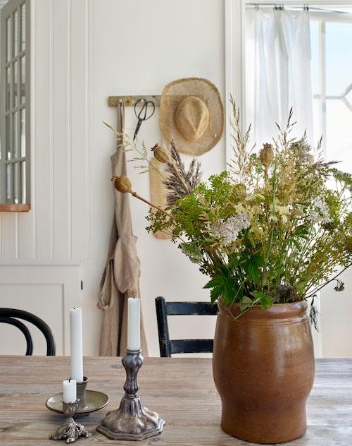 Knoppbrädan i bakgrunden är egentillverkad av drivved. Ljusstakar och vas är loppisfynd.
