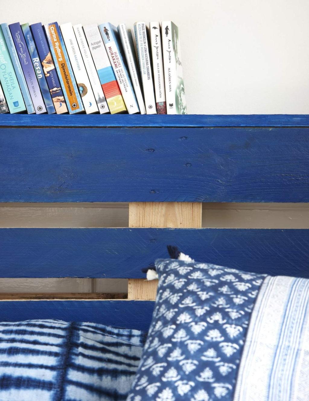 Genom att såga till en brädbit och måla i samma kulör som lastpallen får du en praktisk hylla ovanför sängen, borra och skruva fast den i lastpallen. Kudde, 249 kronor, Indiska.