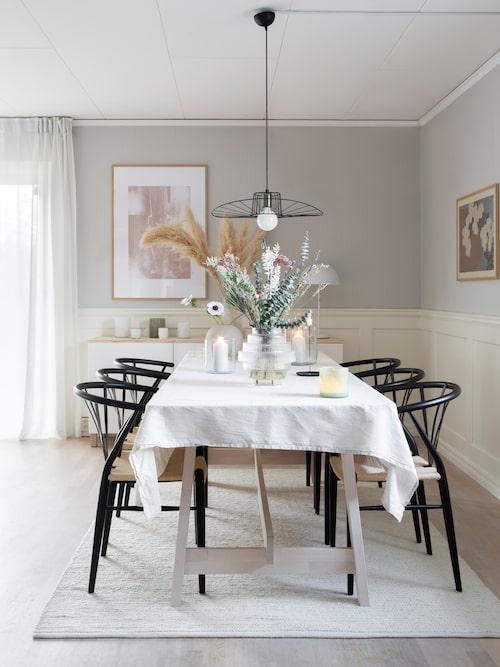 Jenny och Niklas valde svarta stolar för att skapa kontrast till den ljusa grunden kring matplatsen. Matta, Jotex. Stolar, Stalands möbler.  Ljuslyktor, Tellmemore. Duk, Cellbes. Tavla, Dearsam. Tavla till höger Pepperholm. Lampa, Qpviq. Glasvas, Ellos.