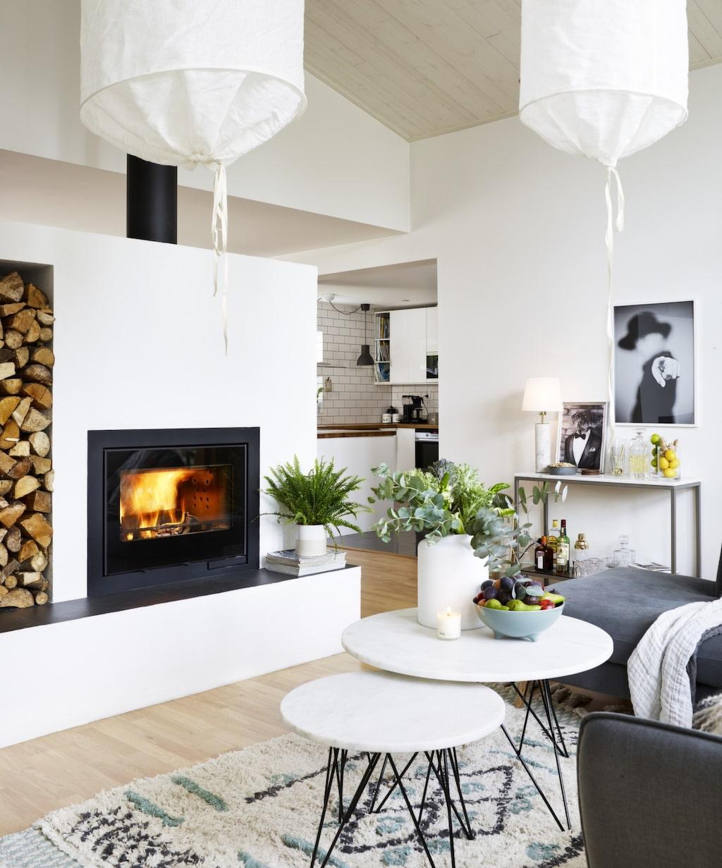 <p>Ombonat vardagsrum i vita toner. Mjuka textilier och runda soffbord och gröna växter mjukar upp de raka linjerna. </p>