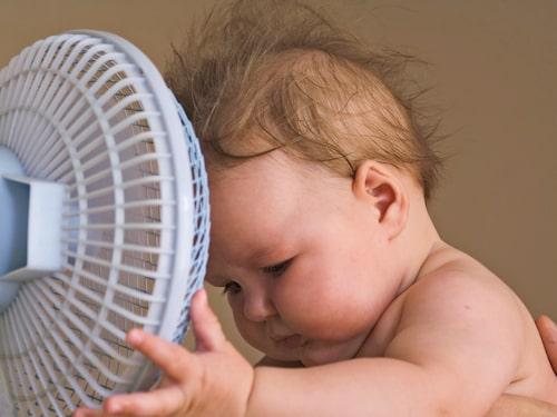 Gör som den här bebisen - svalka dig vid fläkten om det blir för varmt hemma.