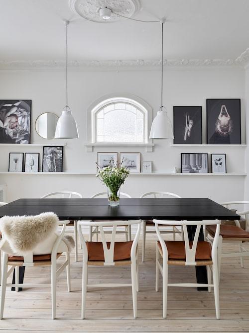 I matsalen har paret satt upp små hyllplan på väggen. På dem kan de arrangera vackra tavlor efter tycke och humör. Mässingsspegeln kommer från Hübsch. Taklamporna kommer från Cecilie Manz.