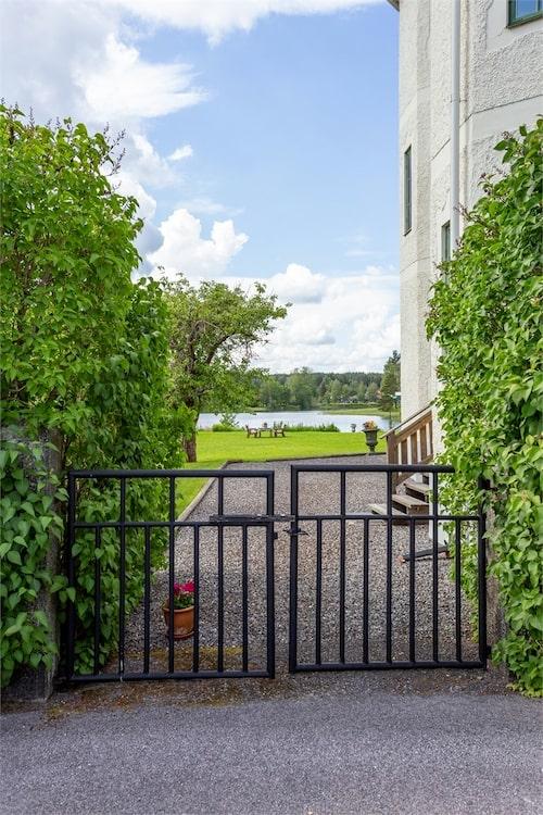 Grind till baksidan som rymmer en stor gräsmatta med egen brygga och uteplats.