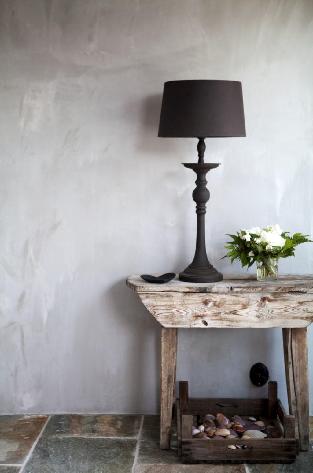 De vackert flammiga och helt matta väggarna gjordes av en blandning av spackel och bruk. Bordet är ett gammalt loppisfynd som förut stod i Eva-Lenas växthus men fick flytta in.  Trätråg med snäckor samlade från resor. Svart lampa från PB home.