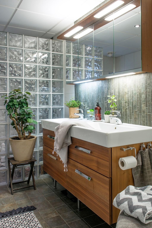 Praktisk förvaring. Badrummet, som är ett kombinerat tvättrum, har en praktisk tvättställskommod och ett spegelskåp. Handdukar från Jysk och matta från H&M home. Växten på pallen är en silveraralia.