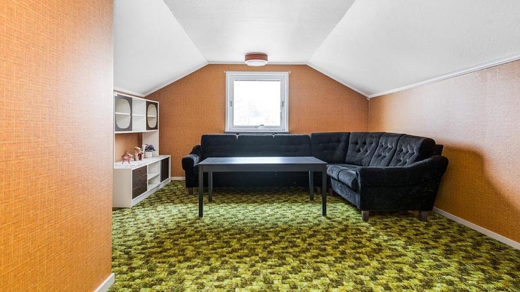 Knallgrön heltäckningsmatta och orange väggar. Ett av två sovrum på vindsvåningen.