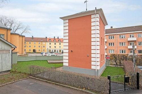 Huset från parkeringen med gräsmatta och fristående altandäck.