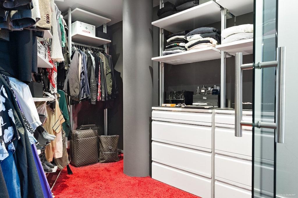Rymlig walk in closet med platsbyggd inredning i form av stänger, hyllplan, och lådor.
