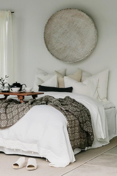 I annexet finns plats för övernattande gäster. Sängkläder i linne, Ikea. Pläd, Olsson & Jensen. Serveringsbricka och fat på väggen, PB Home.