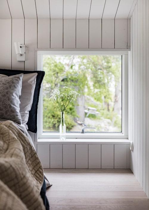 Sovrummet har snedtak och vita väggar som det övriga huset. Blå örngott, påslakan, överkast och glasflaska, Granit. Ljusgrått örngott, H&M Home.