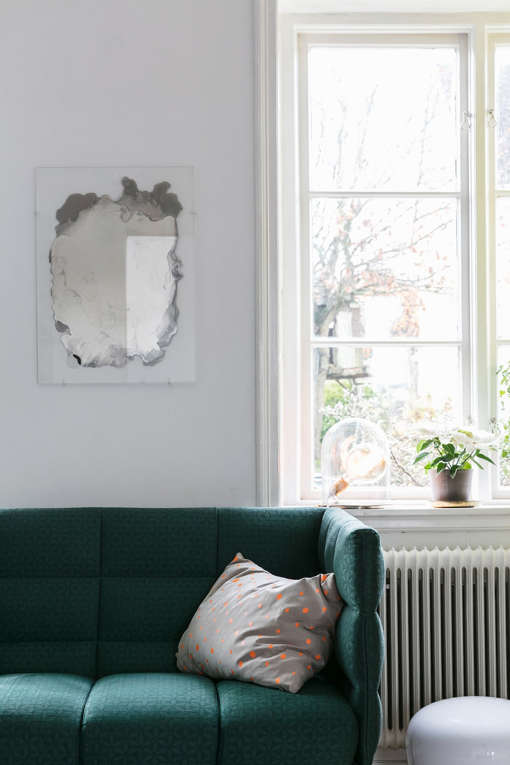På väggen hänger ett spegelkonstverk av Jenny Nordberg som Tina köpt i present till Hans. Grön soffa från Bolia.
