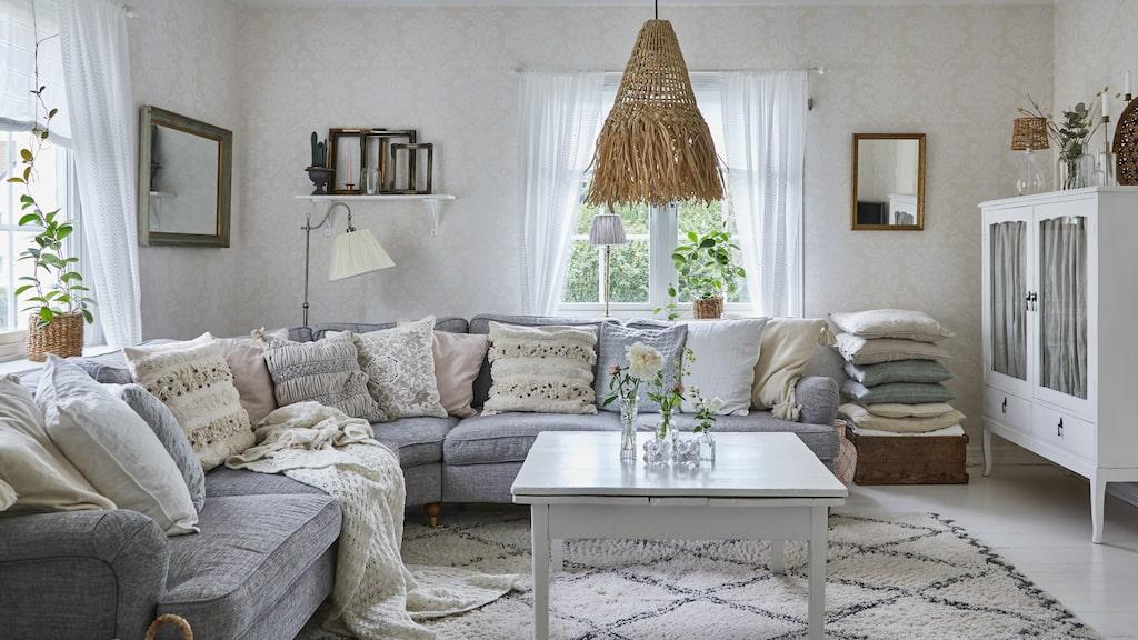 För att skapa en ljusare planlösning har paret öppnat upp mellan vardagsrum och matsal. Nu ryms här en stor soffa utan att det känns för trångt. Kuddar från bland annat Odd Molly och H & M Home. Matta i från Ellos.