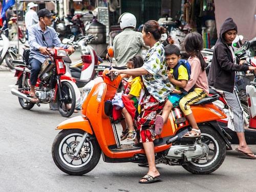 De flesta Phnom Penh-bor har inte råd med bil, men hela familjen får plats på motorcykeln.