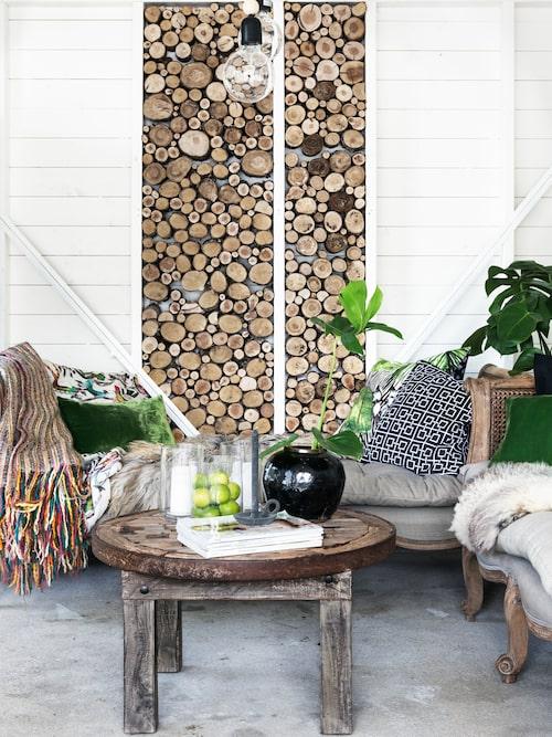 Väggen med vedträn bidrar till en varm och ombonad känsla i uterummet. Bord, soffa och lampor från Herlighet. Kuddar från Karisma interior. Vas från Slettvoll.