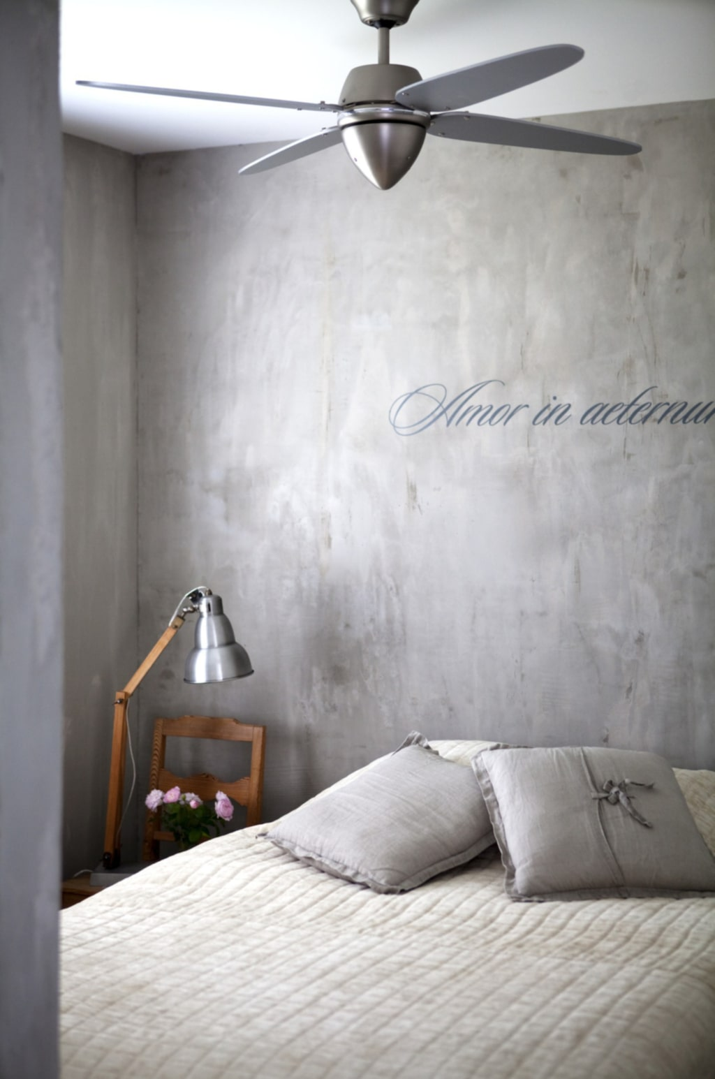I det vilsamma sovrummet finns en ärvd trä stol och på den står en lampa från Bruka. Överkastet kommer från Engelska tapetmagasinet.. Kuddarna i linne kommer från Himla. Takfläkten i borstad aluminium ger skön svalka under varma sommarnätter och ger en kontinental look. I vanliga standarddörrar fälldes skjutdörrs handtag in. De mattsvarta dörrarna hängdes på räls som specialbyggdes av en lokal smed.
