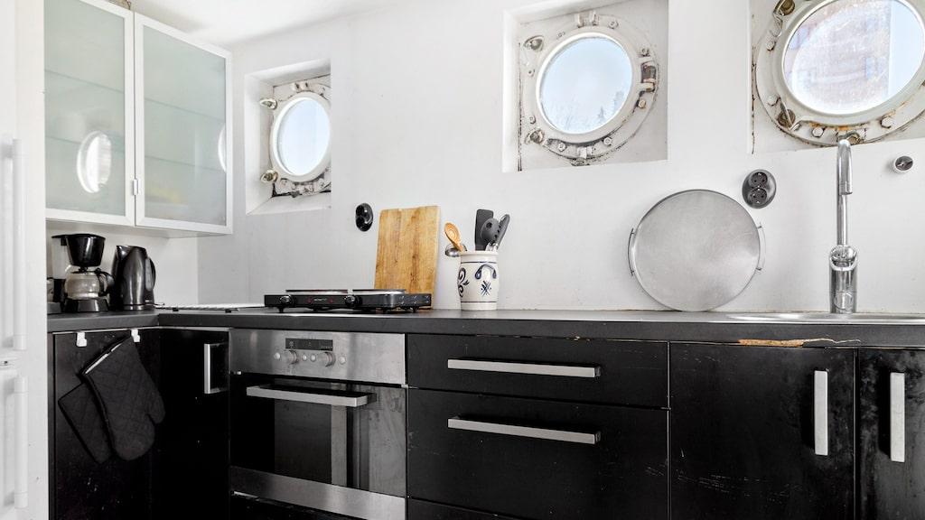 Köket som ligger på entréplan har svarta skåpluckor och lådor, ugn, kyl samt spisplatta.