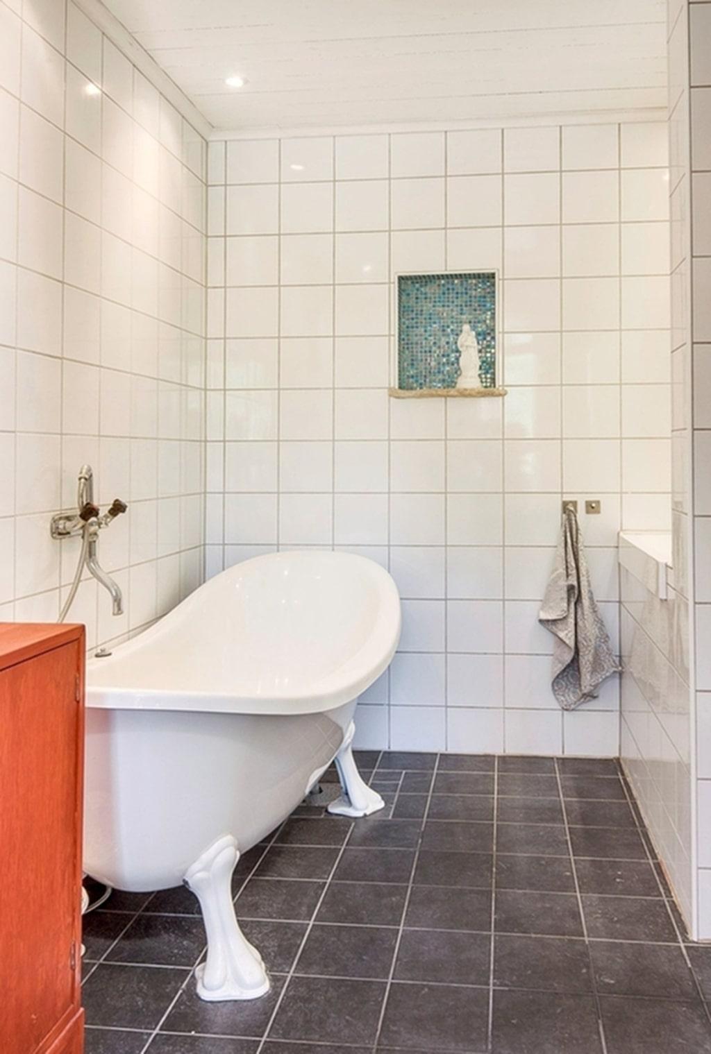Toalett med vitt kakel och badkar.