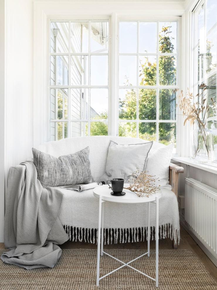 Verandan är en favoritplats, den är ljus och mysig. Brickbord, Ikea. Ljusgrå pläd, Åhléns.