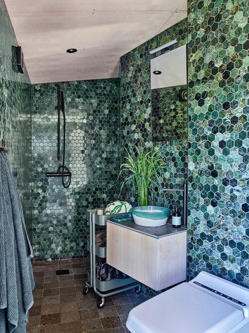 Badrummets väggar är klädda med marmorkakel. Kakel och blandare, Tapwell. Förbränningstoalett Cinderella, Rörtjänst. Spanskt handfat i vitlera, Sidsid.se.