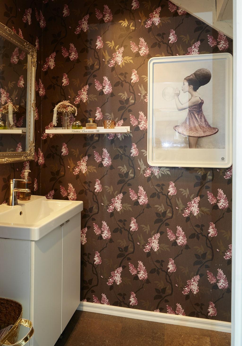 Toaletten under trappen är liten men välkomnande, Tapeten med rosa blommor är från Rusta, tavlan från Fotografiska i Stockholm.