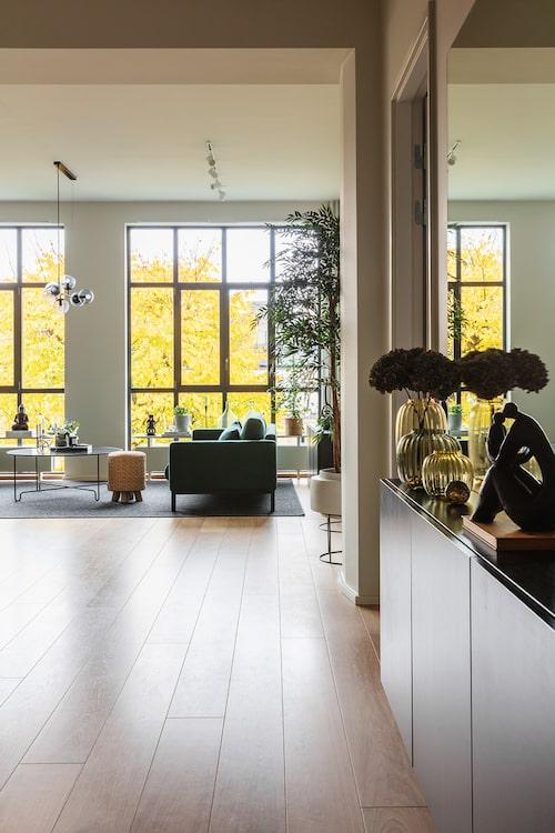 Det första man möts av när man kliver in i lägenheten är det ljusa vardagsrummet och dess gigantiska fönster. I den avlånga hallen finns det mycket förvaring i form av garderober och skåp som familjen själva satt in. Vaser, Kähler. Förvaringsskåp, Ikea. Svart skulptur, köpt utomlands. Glaskula, Cervera.