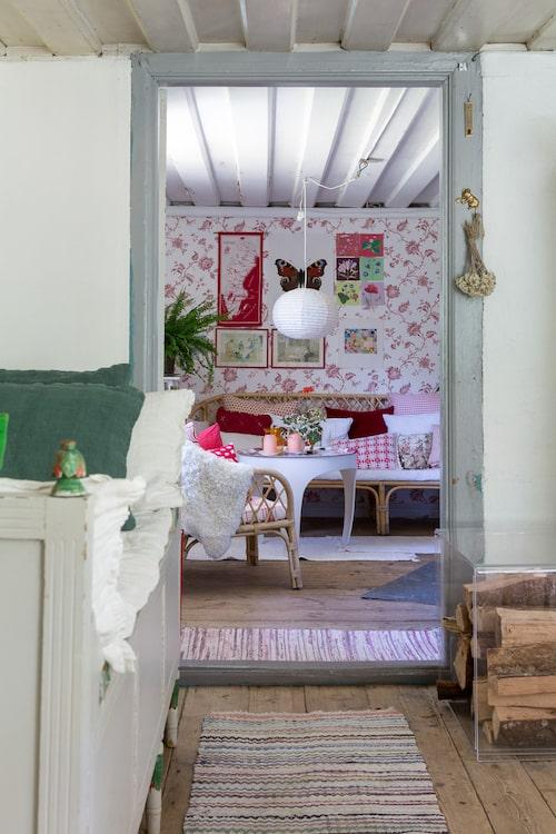 Rummet intill köket är en ombonad myshörna med rottingmöbler och textilier i rött, vitt och rosa. Bord, Svenskt Tenn. Tapet Cape Cod, Carma. Möblerna är loppisfynd eller ärvda.