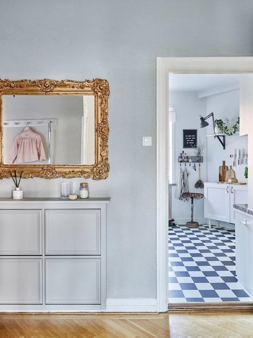 Den guldglänsande spegeln i hallen är ett arvegods från Linneas farmor. Skoskåpet, från Ikea, har fått lister och är ommålat ton i ton med hallens antikgrå väggar. Färg, från Jotun.