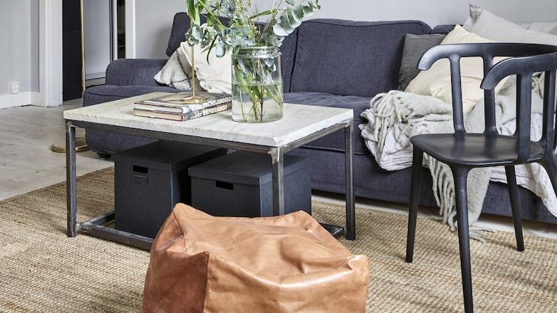 Vardagsrummet är inrett med en mix av grått, mässing och stål. Sisalmattan mjukar upp och binder ihop soffhörnan. Pläd, Cozy living, kuddar,Linum, skinnpuff, Wallboe interior, stol, Ikea, golvlampan är secodn hand, soffa, Mio.