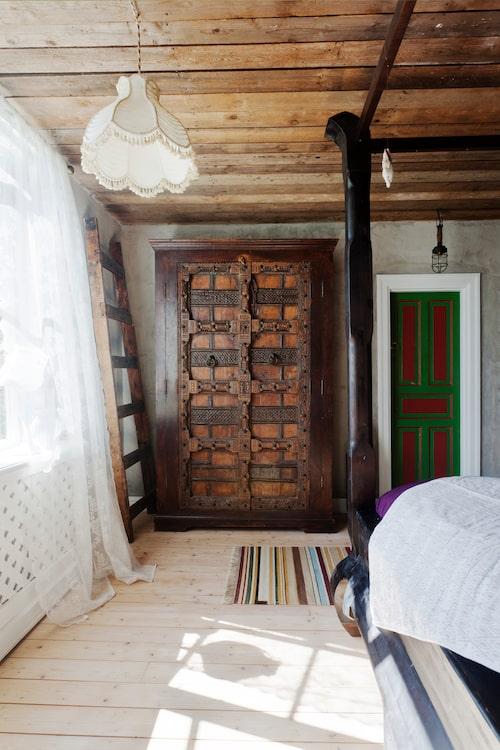 Dörren är originalmålad av husets förra ägare. Taklampan kommer från loppis och skåpet kommer från Nepal.  Sängen har Johan själv byggt.