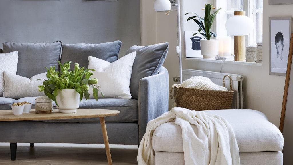 <p>Skandinavisk stil i svala toner. Pläd med bollfrans från Indiska. Svängd soffa från Mio. Soffbord i lackad ek från EM.</p>