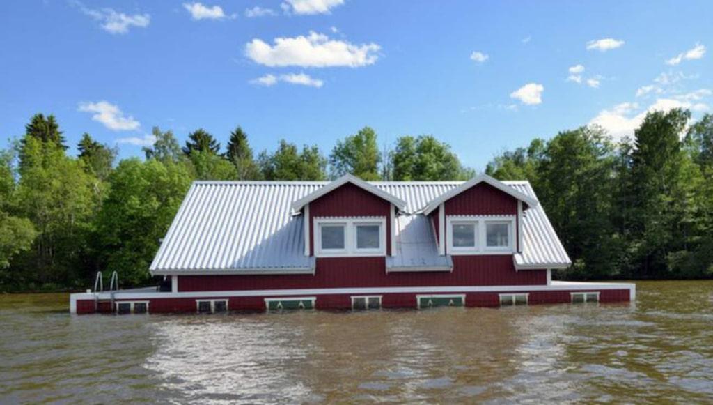 Huset ser ut att vara på väg att sjunka, men det gör det givetvis inte. Det är ritat av konstnären Mikael Genberg och flyter på pontoner.