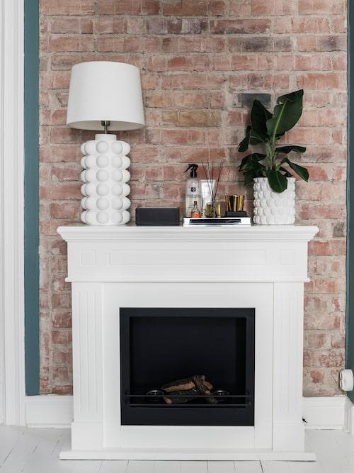 Den vita öppna spisen blir en fin kontrast mot den råa tegelväggen. Lampa och kruka, Hallbergs belysning.