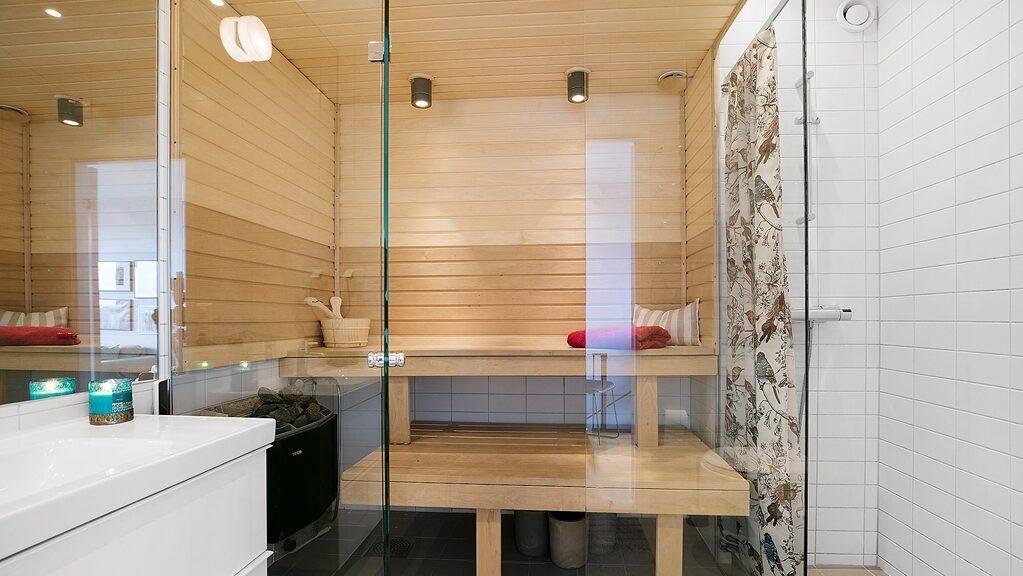 I ett av de två badrummen finns en bastu bakom glasade väggar, samt dusch, wc, handfat och spegel. Spotlights i taket.