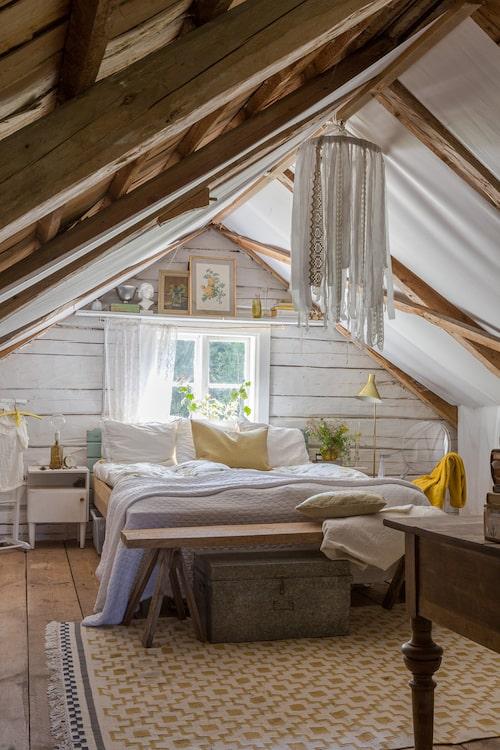 Den ena halvan av vinden är Malins och Johans sovrumsdel. Matta och påslakan, Ikea. Genomskinlig stol, Kartell. Mobilen är gjord av tygremsor.