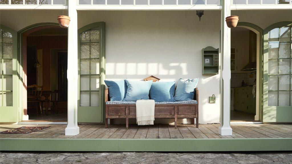 En stor och härlig veranda med pelare och trägolv att sitta på och blicka ut över trädgården. Vackra dörrar från matsal och kök leder dit ut.