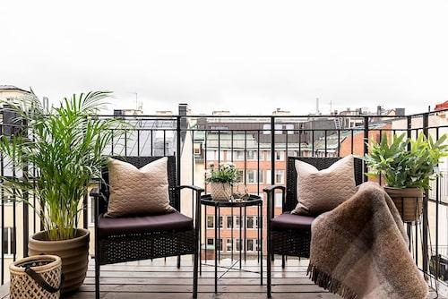 Lägenheten ligger på fjärde våningen. Från balkonen har man utsikt över takåsarna.