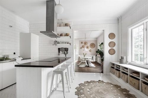 Det vitmålade taket, trägolvet och väggarna ger interiören fullt fokus i ett av de tre köken.