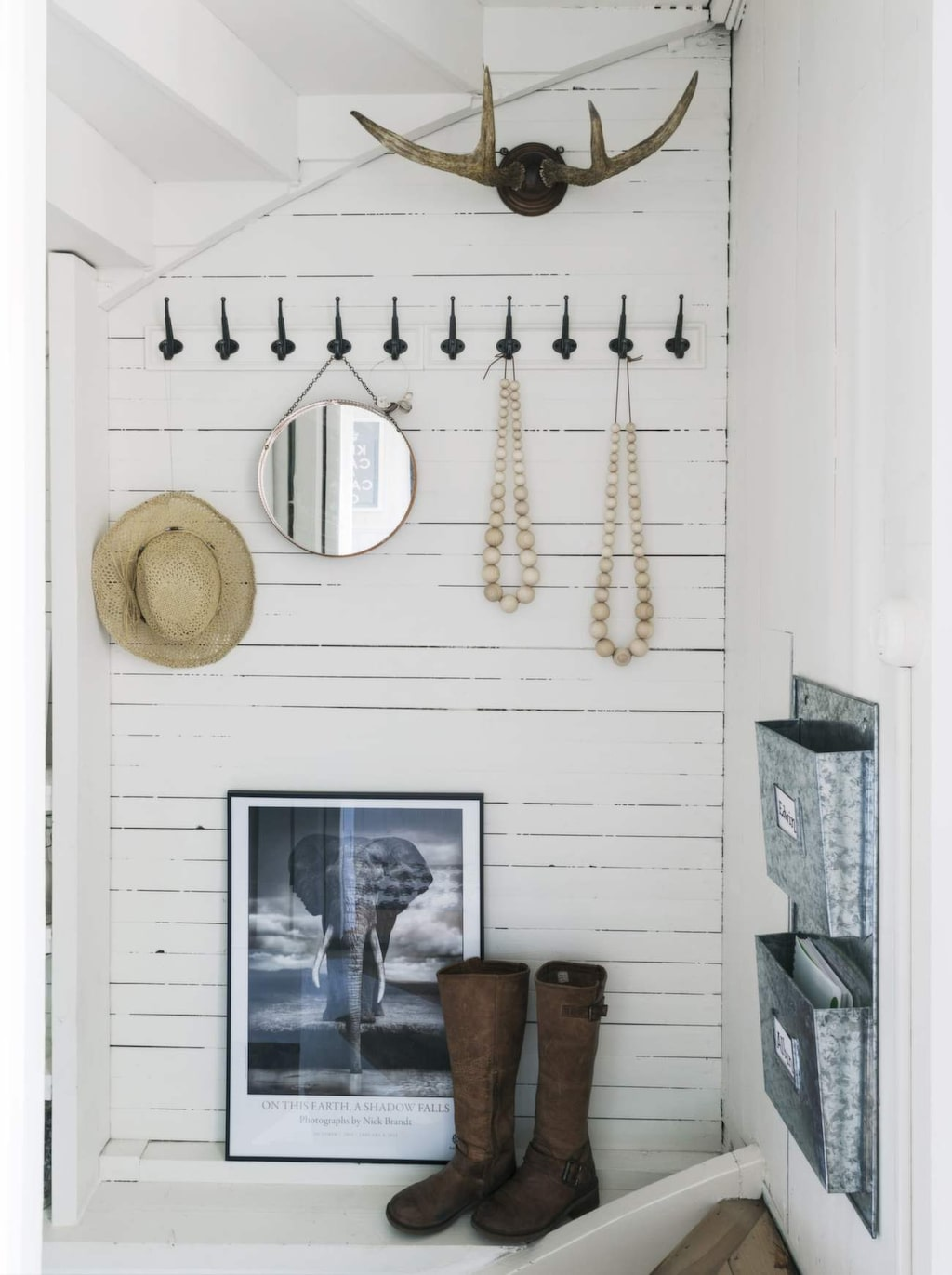 I källartrappan sitter knoppbrädor från Ikea. Spegel från Myrorna, älghorn från Åsas morfar, hatt köpt i England. Halsbanden har Åsa och Ester gjort med träpärlor och läderband från Panduro. Tavlan är från Fotografiska/Nick Brandt. Ram Ikea. Postfacken är från Bruka design och i dem lägger vi viktiga papper som ska ned till killarnas rum.