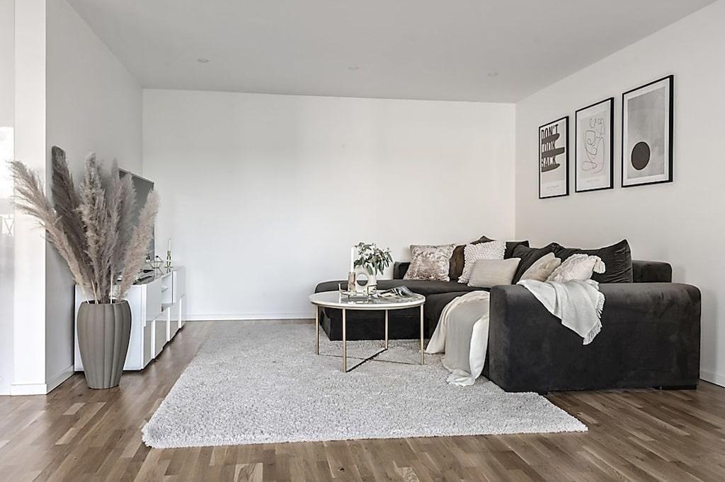 Lägenheten har genomgående parkettgolv och slätspacklade vita väggar.