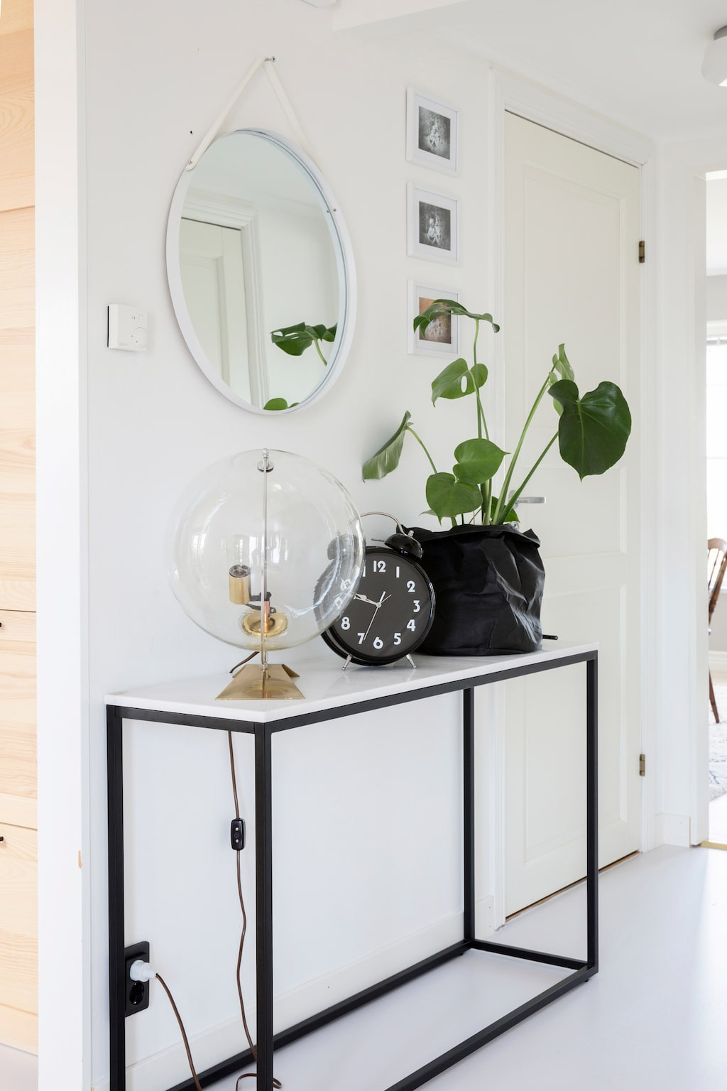 Gröna växter mjukar upp en stramare inredning. På avlastningsbordet i hallen, från Furnituebox, samsas en lampglob från Virvlas med en väckarklocka, från Norrgatans Blommor & Interiör, med en monstera i svart säck.