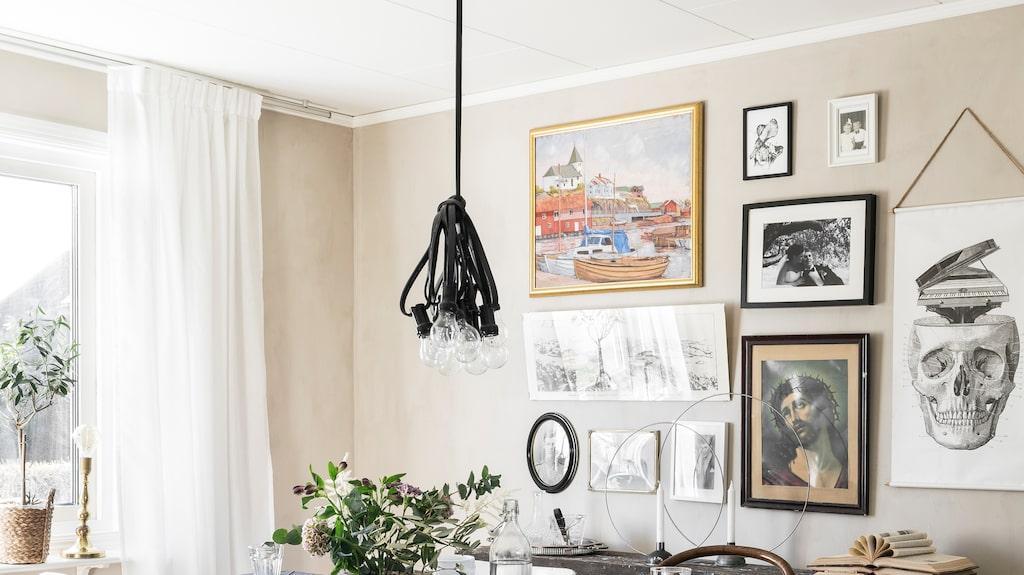 """Den ljusa matsalen är hemtrevlig och personligt inredd med en charmig tavelvägg. Runt bordet står udda stolar. De vitmålade pinnstolarna kommer från Elinas morfars hus och har använts av släkten i flera generationer. """"Taklampan är en ljusslinga från Lagerhaus som min Joseph har buntat ihop och format till en taklampa"""", säger Elina."""