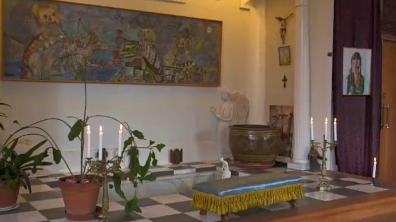 Framme vid altaret finns ett nedsänkt hål fyllt med vatten som fungerar som en fontän.