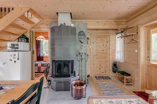 Golv, tak och väggar går i naturliga toner som ger eldstaden och interiören fullt fokus.