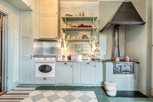 I det charmiga köket med grönmålade luckor finns en modern spis från Smeg och en gammal vedspis.