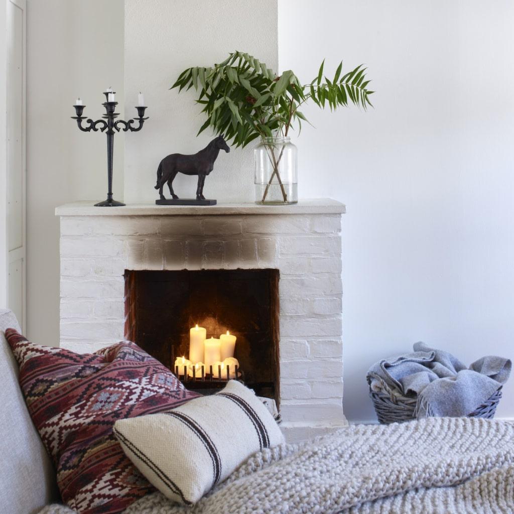 Vid brasan. Eldstaden ska renoveras. Röd kelimkudde från Pb home. Vit kudde från Marocko design. Ullpläd från By Pias.