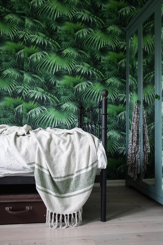 Tapeten från Midbec ger liv åt Viras rum och går igen även i spegeldörrarnas reflektion. Under sängen ryms prylförvaring i resväskor fyndade på loppis.